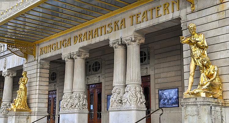 En bild på Dramatens framsida. Byggnaden är gammal. Den har guldfärgade statyer på sidorna.