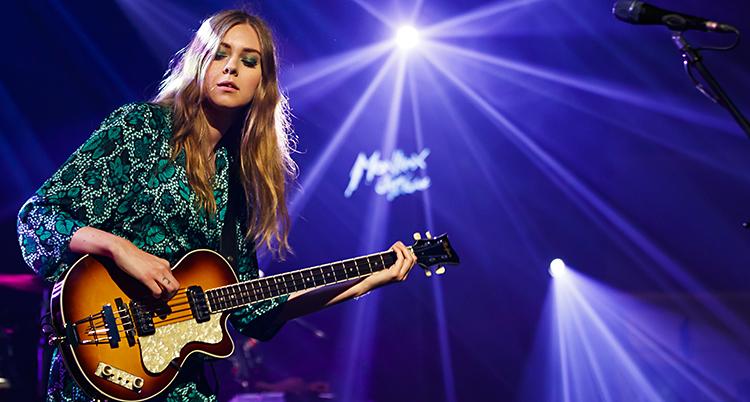 Hon blundar och spelar på en gitarr.