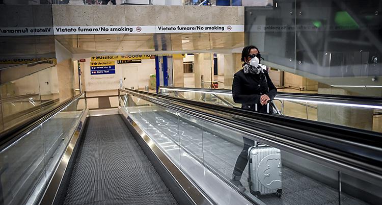 En kvinna med mask står upp i en rulltrappa. Hon har en resväska framför sig.