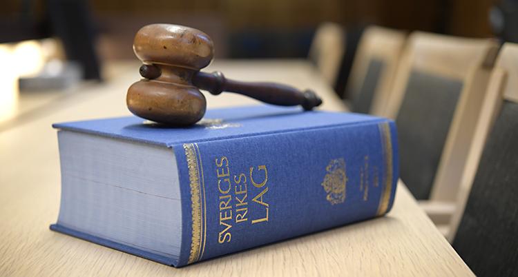 Sveriges lagbok ligger på ett bord. En domares klubba ligger ovanpå boken.