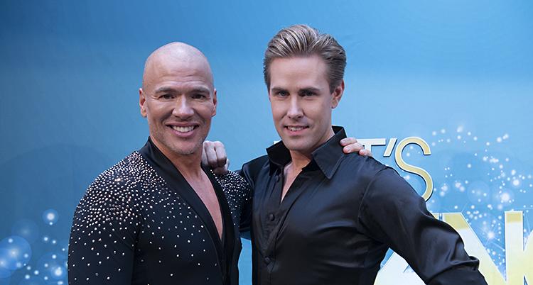 Två män ler och tittar in i kameran. Mannen till vänster har rakat huvud. Mannen till höger har brunt hår som är kammat bakåt.