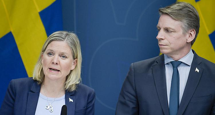 Hon talar i en mikrofon. Han tittar på henne. Bakom dem syns delar av Sveriges flagga i gult och blått.