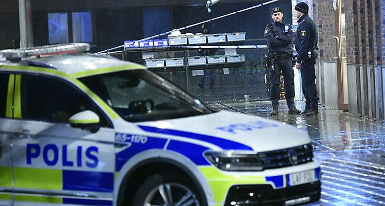 En polisbil framför en avspärrning där det står två poliser.