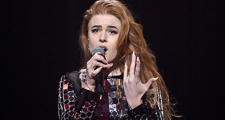 En kvinna med rött hår som sjunger i en mikrofon.