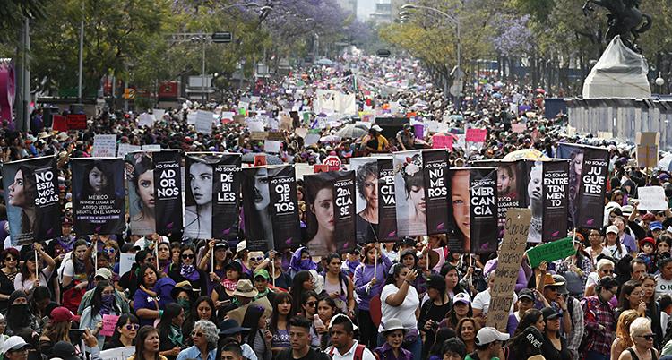 Massor av kvinnor går längs en bred gata kantad med träd