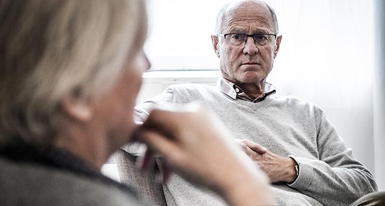 En man sitter ner. Han ser allvarlig ut. Han har glasögon och en beige tröja.