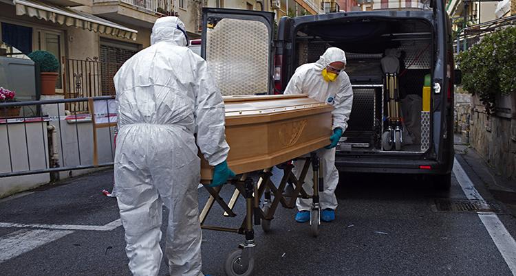Två personer är klädda i vita skyddskläder. De bär in kistan i en bil.
