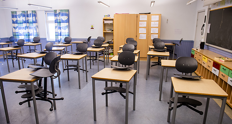 Bilden visar ett klassrum med tomma bänkar och stolar.