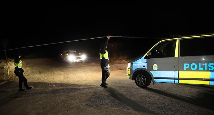 Det är mörkt. En polisbil lyser i mörkret.