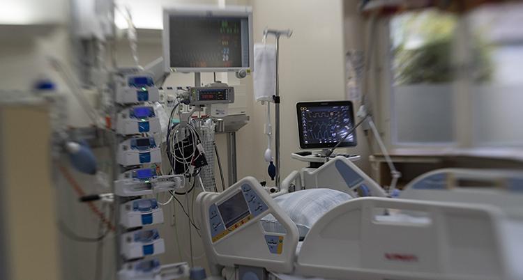 En säng på ett sjukhus. Den har flera skärmar och sladdar runt sig.