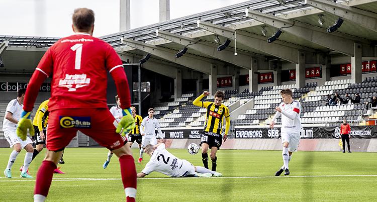Häcken anfaller. En spelare försöker att skjuta. En back ligger ner och försöker att stoppa honom.