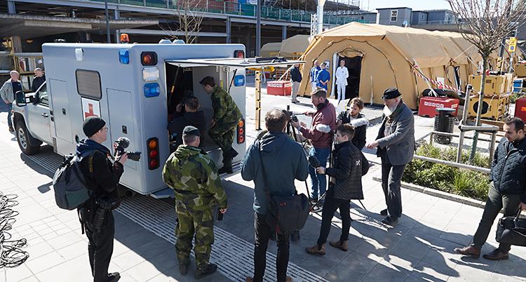 Folk samlade vid en ambulans. I bakgrunden ett stort brunt tält.