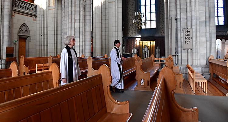 Tomma bänka i kyrkan. Två präster i vita kläder går genom kyrkan