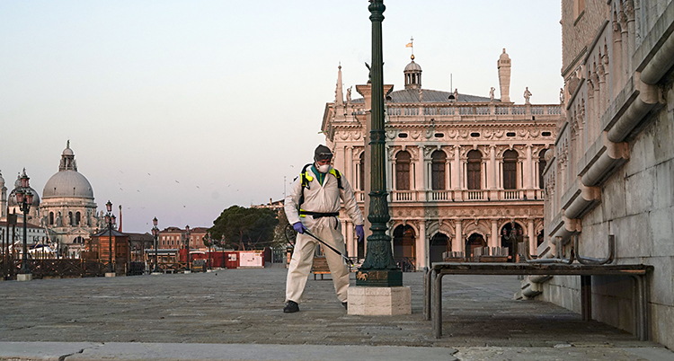 En man i vita skyddskläder sprutar något på en lyktstolpe.