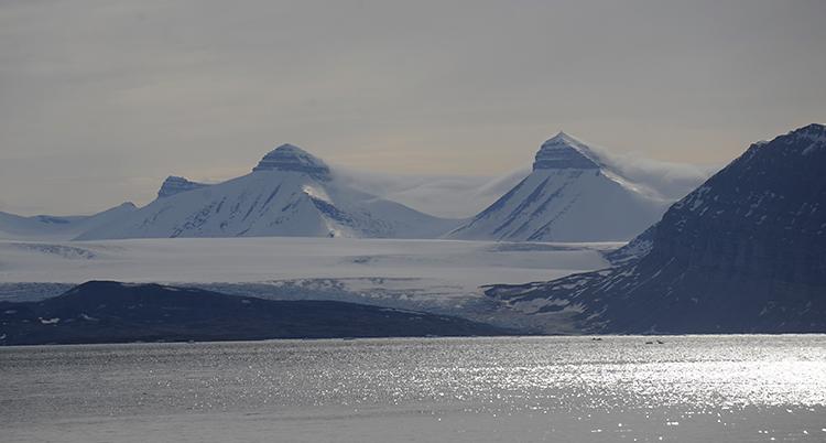 vita fjäll i bakgrunden, i förgrunden hav med sol som speglar sig.