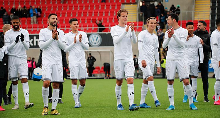 Flera spelare klappar i händerna för att tacka sina fans. De står på en fotbollsplan. De har vita matchkläder.