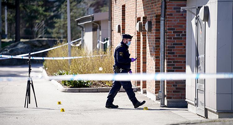 Bilden är tagen utomhus vid en skola. Poliserna har satt upp ett avspärrningsband. Bakom bandet går en polis med ett munskydd.