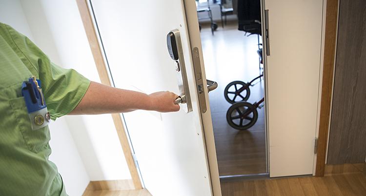 en vårdpersonal håller upp en dörr där man kan skymta en rollator. Ansiktet på vårdpersonalen syns inte, bara armen på dörren.