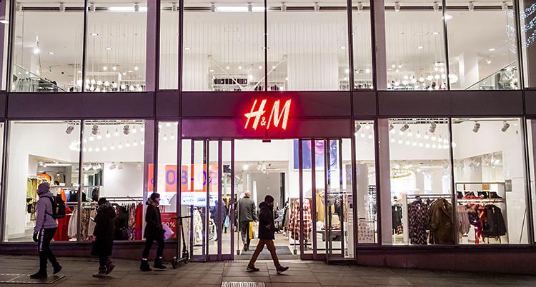 En bild på en av H&Ms affärer. Bilden är fotad en mörk kväll. Vi ser HMs fasad. Folk går förbi utanför skyltfönstren. HMs logga lyser röd ovanför entren.