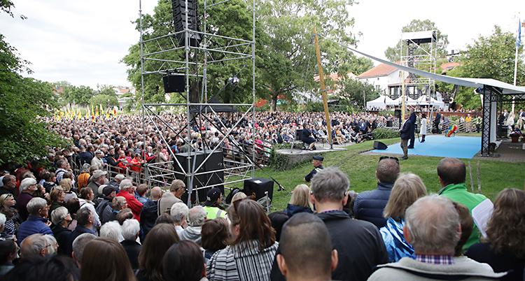 Många människor framför en scen i en grön park