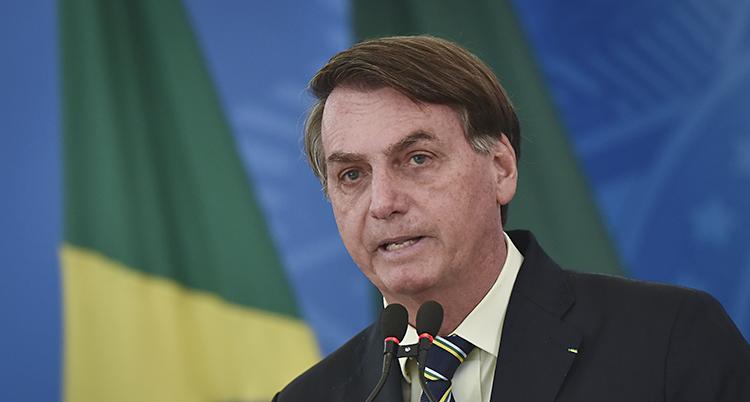 Han pratar i mikrofon framför en brasiliansk flagga