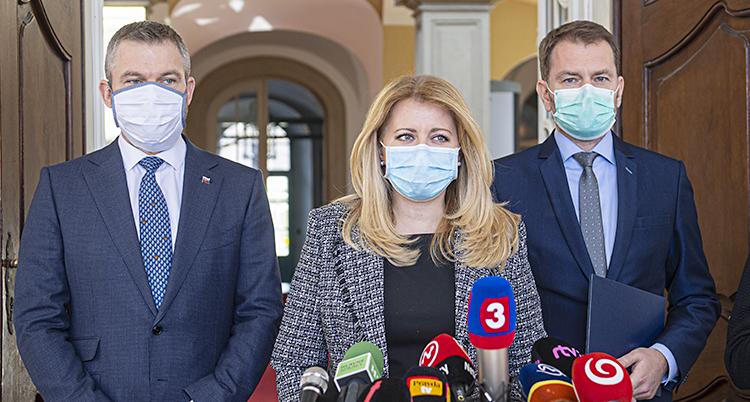 Två män och en kvinna står i kavajer och enkla skydd för munnen