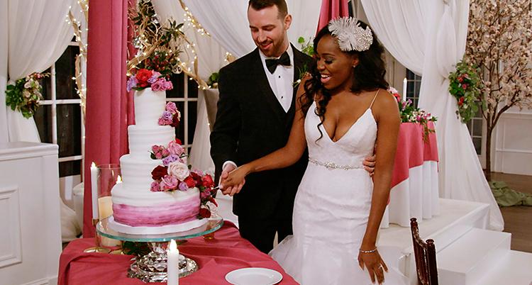 En man och en kvinna skär i en bröllopstårta. Mannen har kostym och kvinnan har vit klänning.