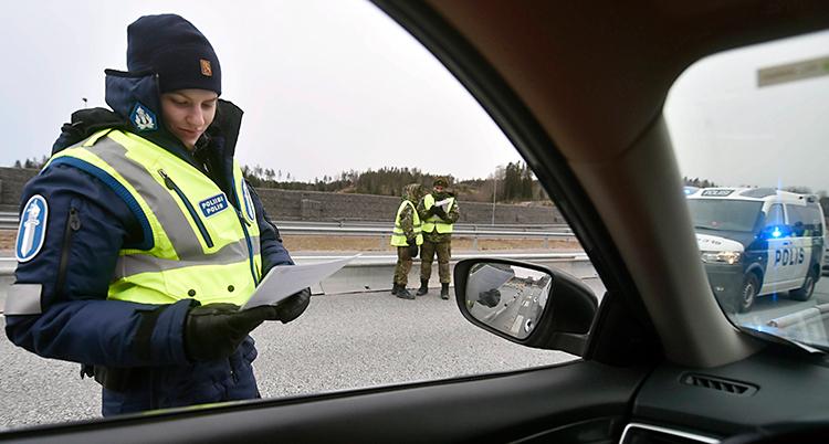Bilden är tagen inuti en bil. Utanför bilen står en polis och gör en kontroll. Lite längre bort står två andra poliser.