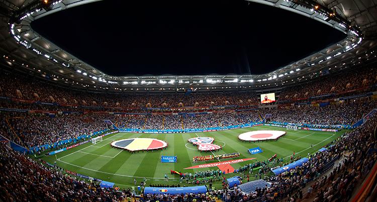 Bilden är tagen från en läktare på en arena. Man ser en grön plan för fotboll. På planen syns flaggor från två länder. På läktarna finns mycket publik.