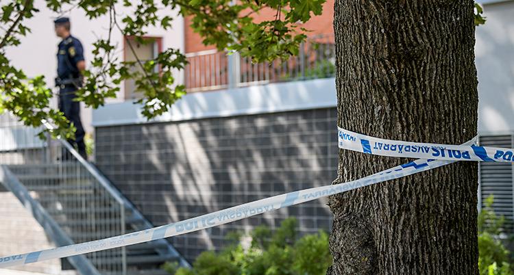 Bilden är tagen utomhus. Det är sommar. Man ser ett lägenhetshus. Poliserna har sprärrat av platsen med vita och blå band. I bakgrunden står en polis.