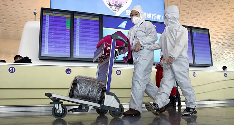 Två personer går på en flygplats. De har skyddskläder och skydd för munnen. En av dem skjuter en vagn med en resväska.
