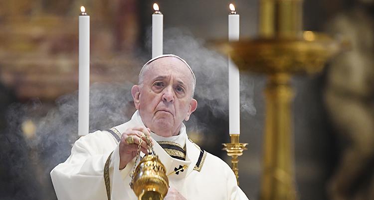 En gammal man i vit dräkt håller i en skål med rökelse