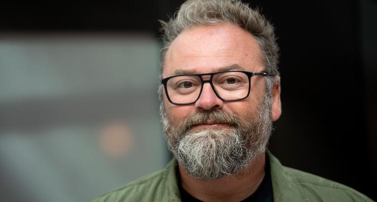 En nära bild på honom. Han har grått skägg och svarta glasögon.