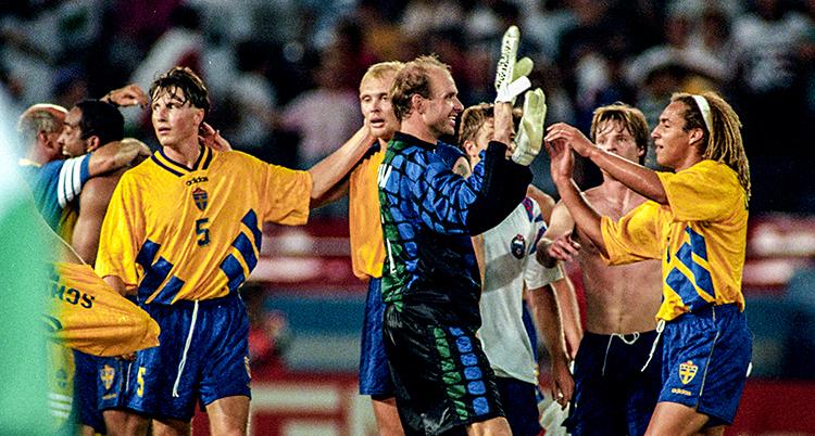 Bilden är från en match i fotboll. Matchen är slut. Sveriges spelare jublar tillsammans.