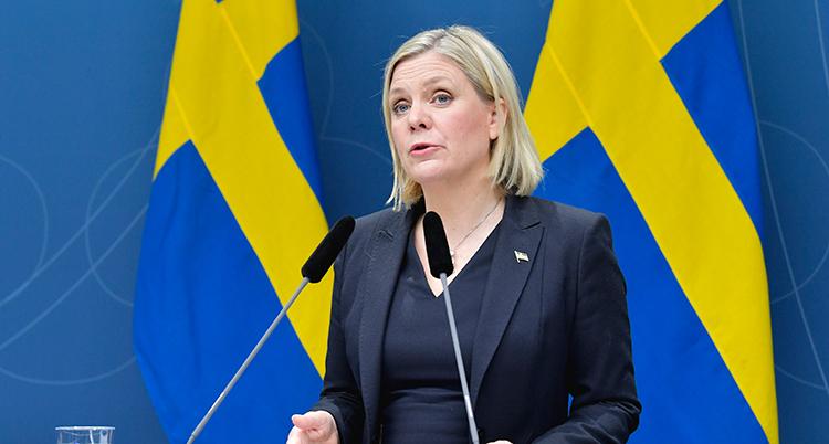 Magdalena Andersson talar. Bakom henne är två svenska flaggor