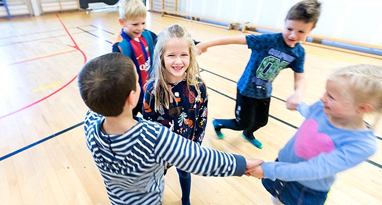 Fem barn är på ett gymnastikgolv. Fyra av barnen håller varandra i hand i en ring. De springer runt. I mitten står det femte barnet och ler mot kameran.