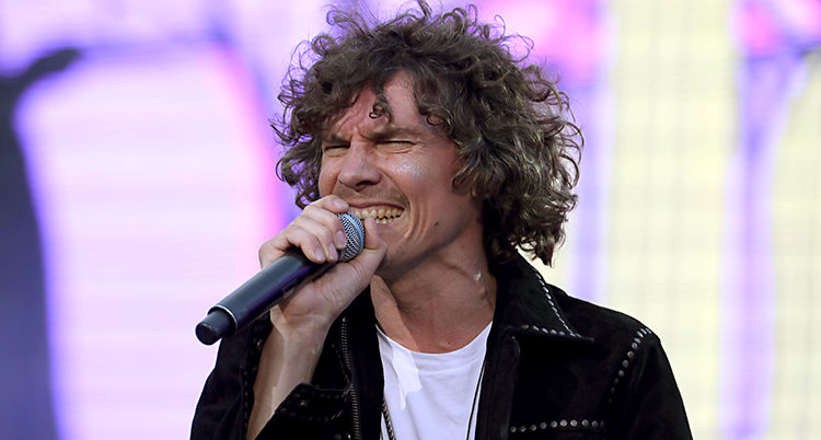 Det är en närbild på Håkan. Han har stort lockigt hår. Han sjunger i en mikrofon och blundar med ögonen.