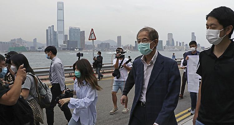 En äldre man med munskydd går på en gata omgiven av andra människor och fotografer.