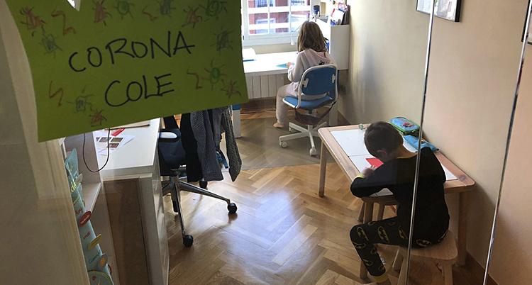två barn sitter inne framför varsin bänk och gör läxor. Vi ser dem fotade uppifrån. Snett i förgrunden hänger en lapp där det står något om corona på spanska.
