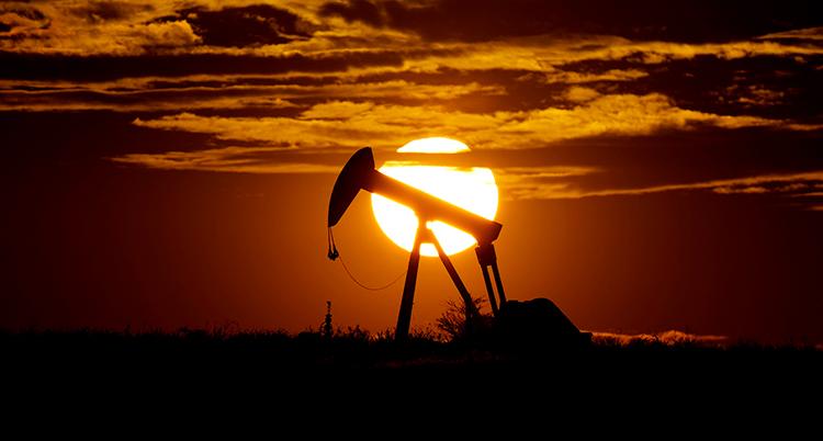 Oljepumpen syns långt bort medan solen går ner
