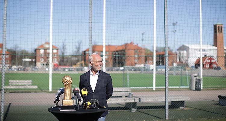 En man står framför en fotbollsplan. Han har flera mikrofoner framför sig på ett bord.