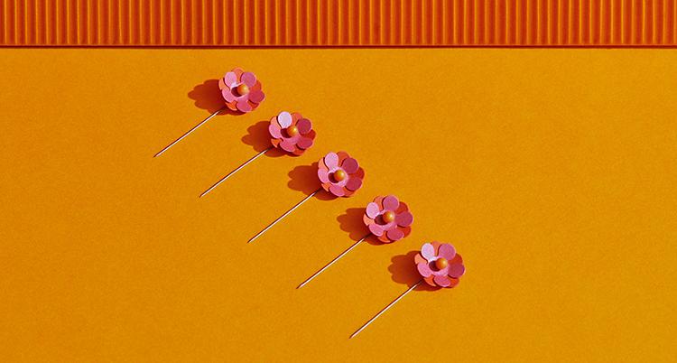 Fem stycken majblommor ligger på en orange bakgrund. Blommorna är rosa och orange. Alla blommor sitter på en liten pinne av metall.