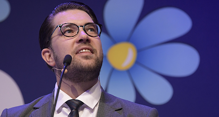 Jimmie åkesson tittar upp. Bakom honom syns SD:s blå blomma.