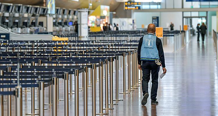 En ensam man går i en stor hall på flygplatsen.
