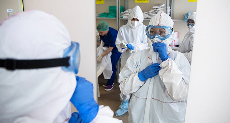 Människor som jobbar på ett sjukhus byter om till skyddskläder. De har vita dräkter och glasögon som skyddar ögonen.