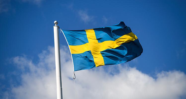En svensk flagga vajar i vinden på en flaggstång. Himlen är blå med några moln.