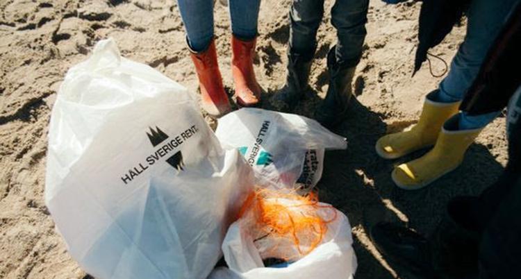 Vi ser ben klädda i stövlar på en strand. Bredvid ligger flera påsar med skräp