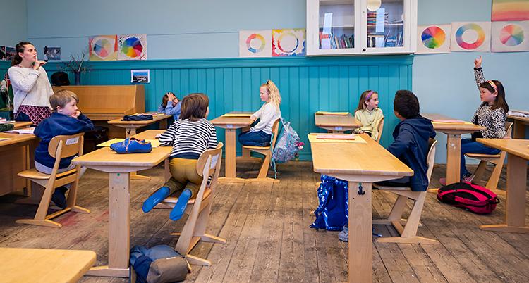 Ett klassrum. En lärare står upp. Flera elever sitter i sina bänkar. De går i tredje klass.