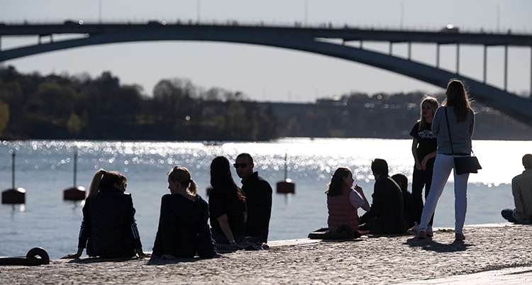 en varm sommardag vid havet. Folk sitter på en strand.