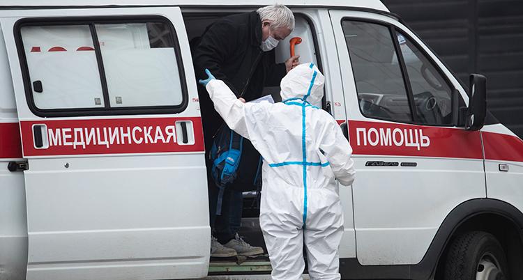 En man med munskydd får hjälp ur en ambulans av en skyddsklädd vårdpersonal.